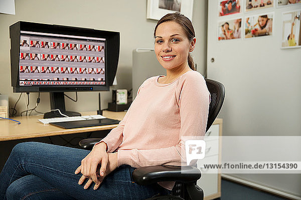 Young woman sitting in home office with computer