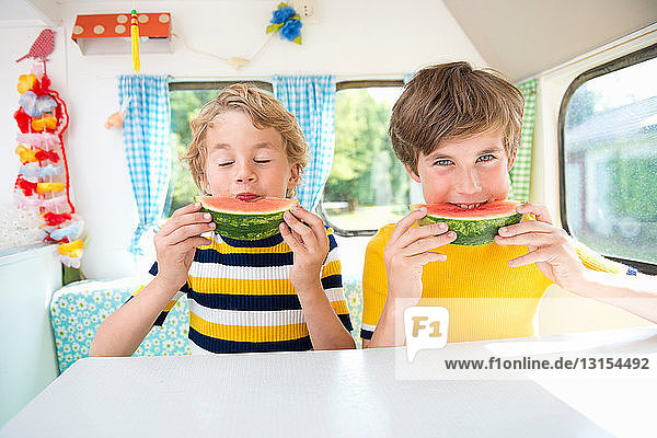Boys eating watermelon in caravan  portrait