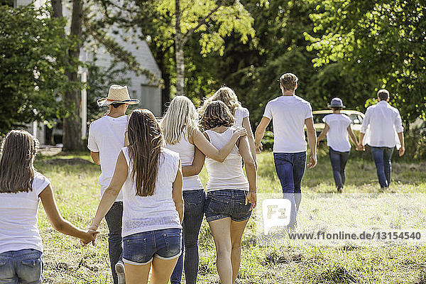 Group of people walking through forest  rear view