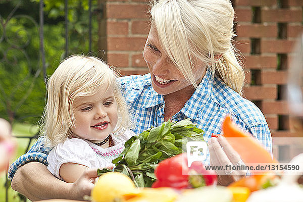 Mother and toddler daughter preparing food at garden table