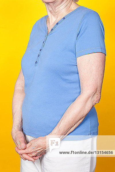 Senior woman with hands clasped  studio shot