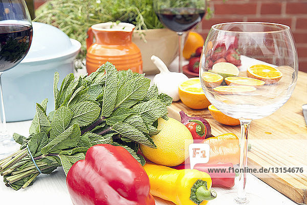 Still life of garden table with herbs  fruit  vegetables and red wine