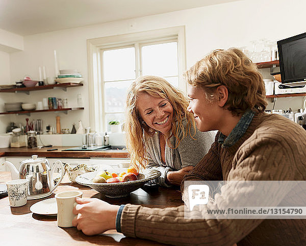 Mother and teenage son sitting at kitchen table