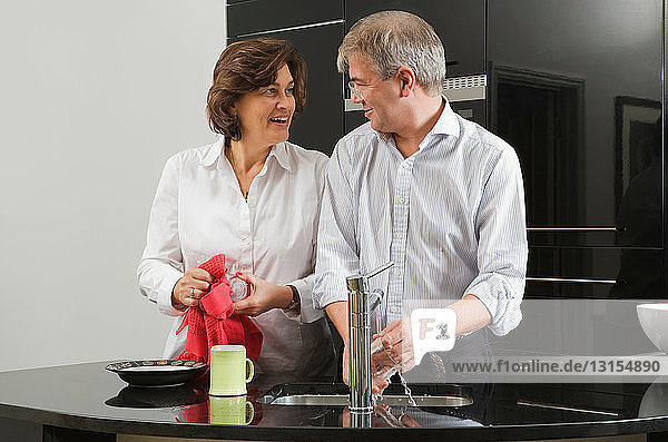 Mature couple washing up together