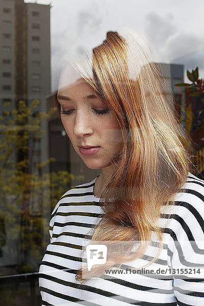 Young woman through window