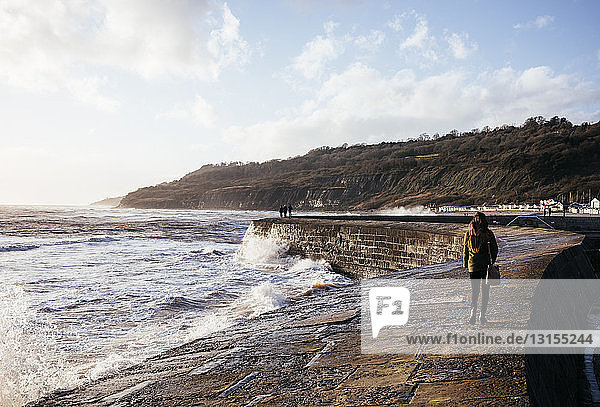 Rear view of young woman strolling along 'The Cobb' harbour wall  Lyme Regis  Dorset  England