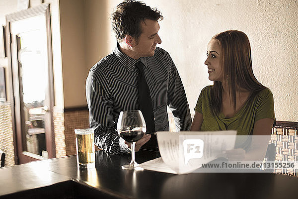Businessman and woman looking at contract in a wine bar