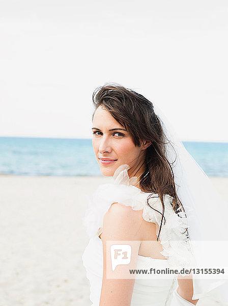 bride on beach looking at viewer