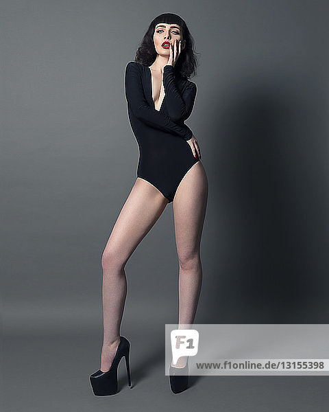 Portrait of young woman wearing bodysuit and high heeled shoes