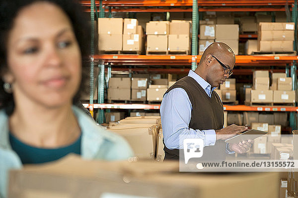 Male warehouse manager using digital tablet  woman in foreground