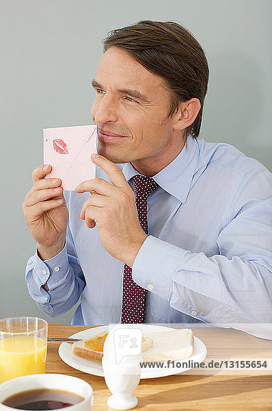 man taking a smell at a love letter