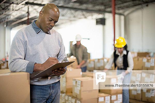 Male warehouse worker holding clipboard