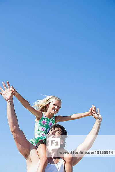 daughter and father on beach playing