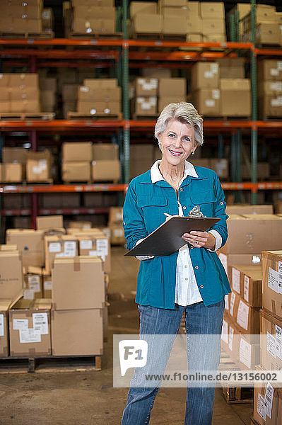 Portrait of female warehouse worker with clipboard