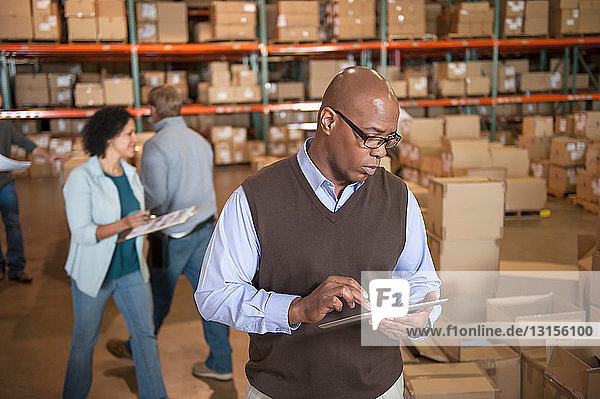 Male warehouse manager using digital tablet
