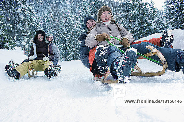 Teenagers riding sled in the snow