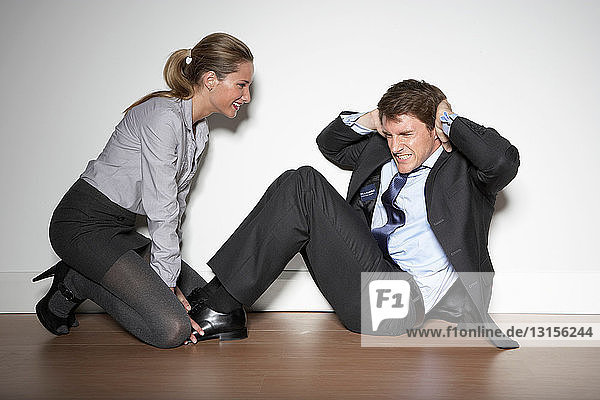 Woman helping business man exercise