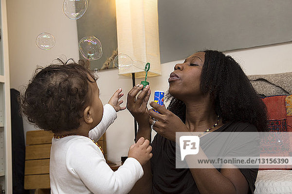 Mid adult woman and toddler daughter blowing bubbles