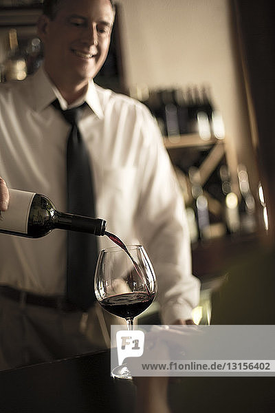 Bartender pouring red wine in bar