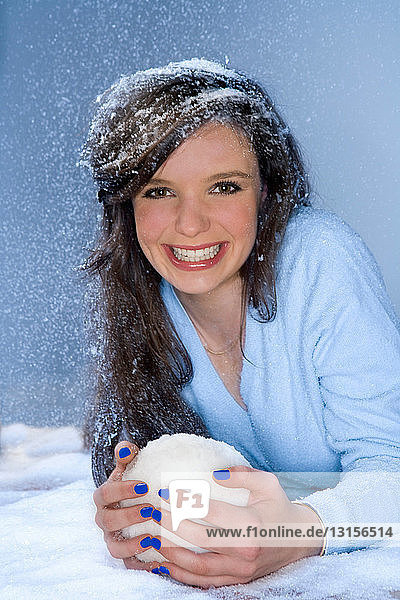 Young woman portrait holds snowball Young woman portrait holds snowball
