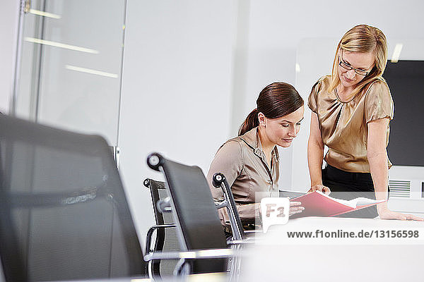 Businesswomen sitting at conference table looking at book
