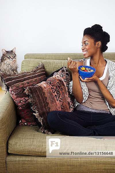 Young woman having breakfast  looking at cat