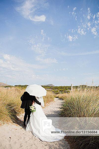 bride and groom walking under parasol