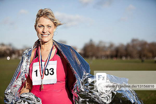 Mid adult woman wearing medal and foil blanket in park