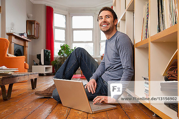 Young man sitting on wooden floor using laptop