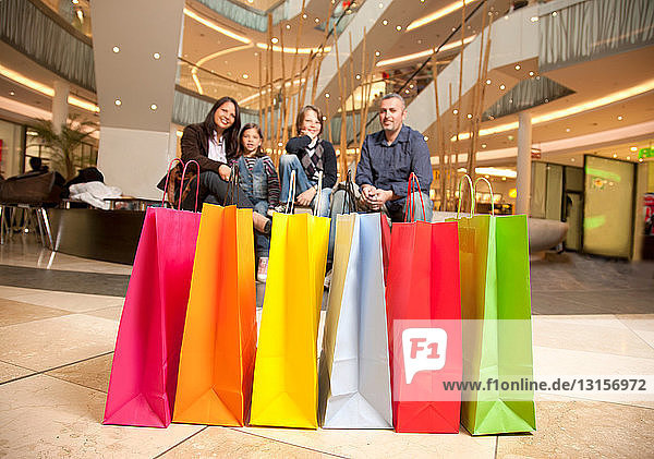 Colorful bags in front of resting family
