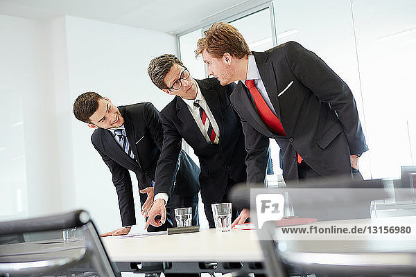 Businessmen leaning over conference table pointing at paperwork
