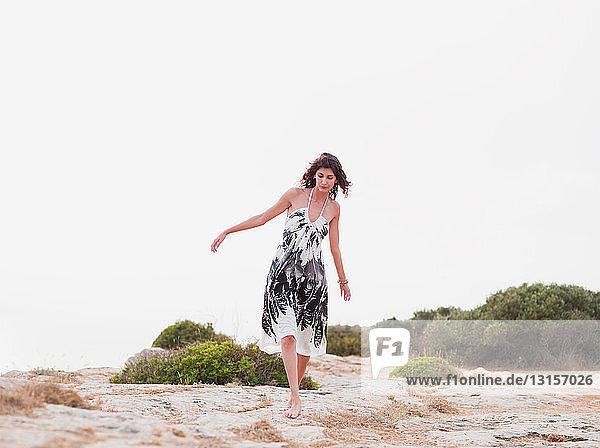 woman in dress walking in the sand