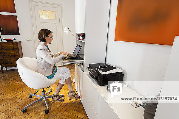Mature businesswoman on office chair typing on laptop in apartment