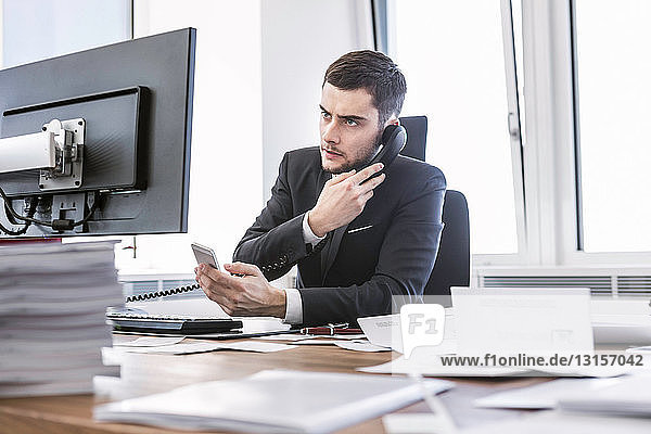 Businessman sitting at desk with computer and paperwork  using smartphone Businessman sitting at desk with computer and paperwork, using smartphone