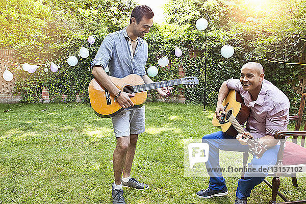 Two male friends playing acoustic guitar in garden