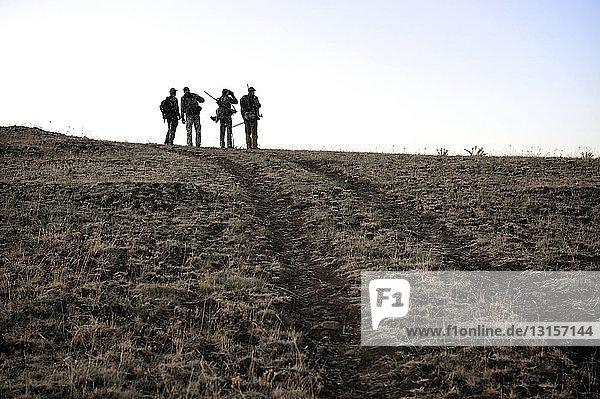 Four deer hunters on top of hill  John Day  Oregon  USA