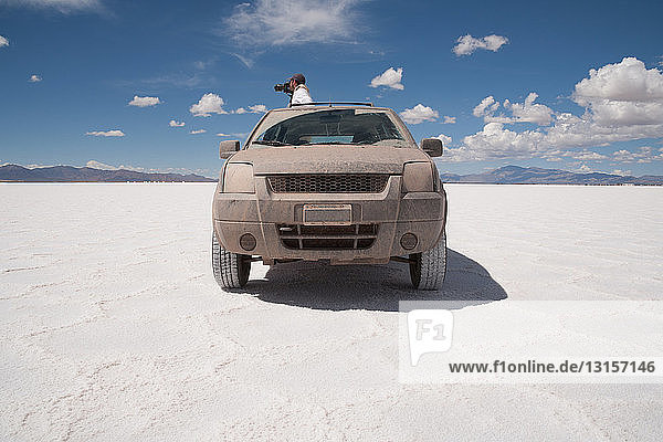 Photographer taking photographs from car in a salt field  Salinas Grandes  Cordoba Province  Argentina