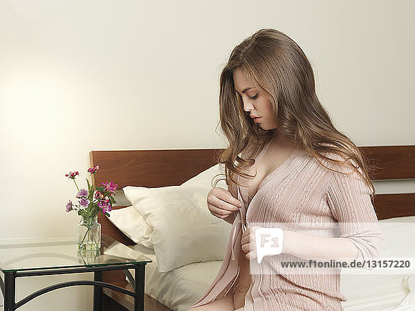 Voluptuous young woman unbuttoning cardigan on bed