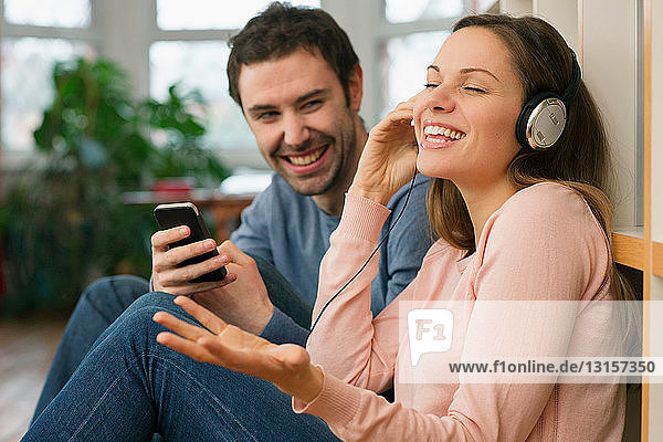 Young couple laughing  woman wearing headphones