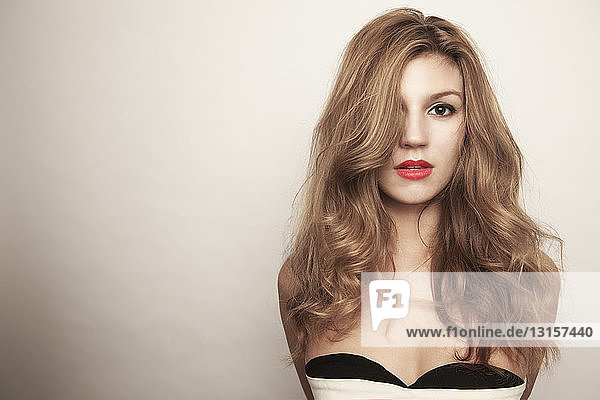 Studio portrait of beautiful sultry young woman with long hair