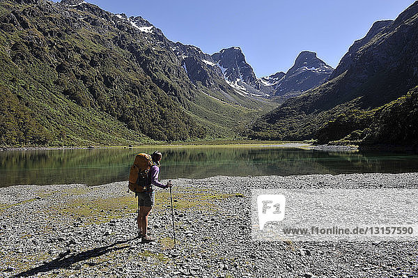 Woman standing by lake in mountains  New Zealand