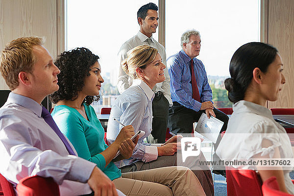 Office workers taking notes in meeting room