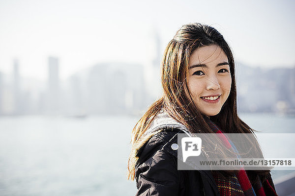 Portrait of young woman wearing checked scarf and leather jacket  looking at camera