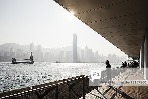 Silhouetted side view of young woman standing looking out over water at skyline  Hong Kong  China