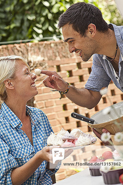 Young couple fooling around with meringue at garden party