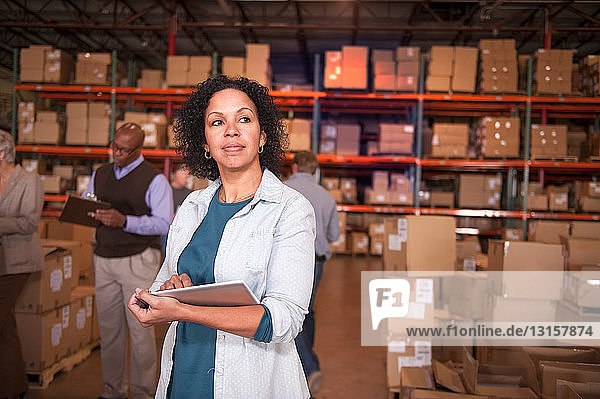 Female warehouse worker using digital tablet