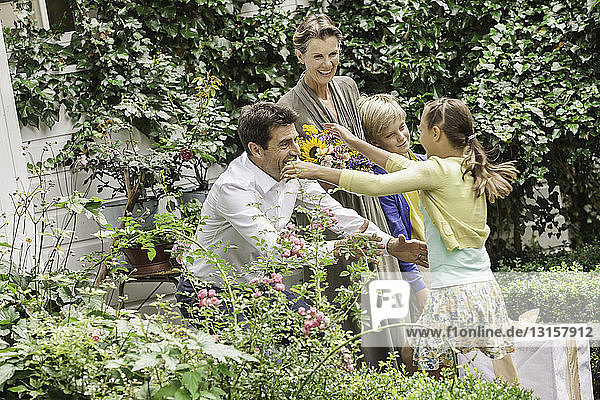 Mature couple greeting grandchildren in garden
