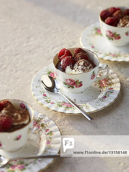 Chocolate mousse with raspberries and cream in vintage tea cups