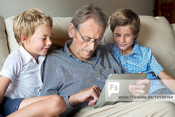 Grandfather and grandsons looking at digital tablet