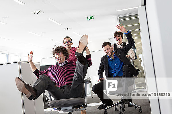 Office workers pushing men on office chairs
